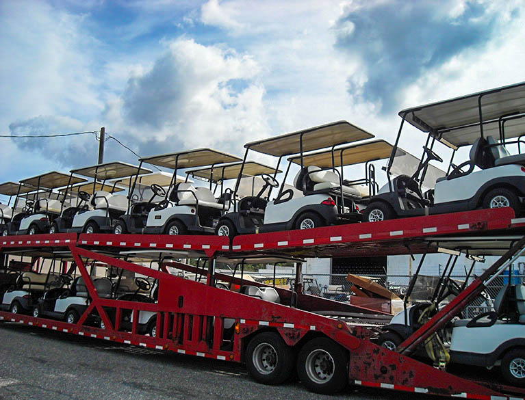 White golf carts on double decker trailer image